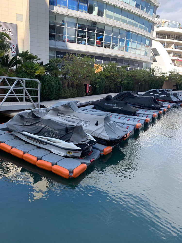floating dock with lots of jet skis moored