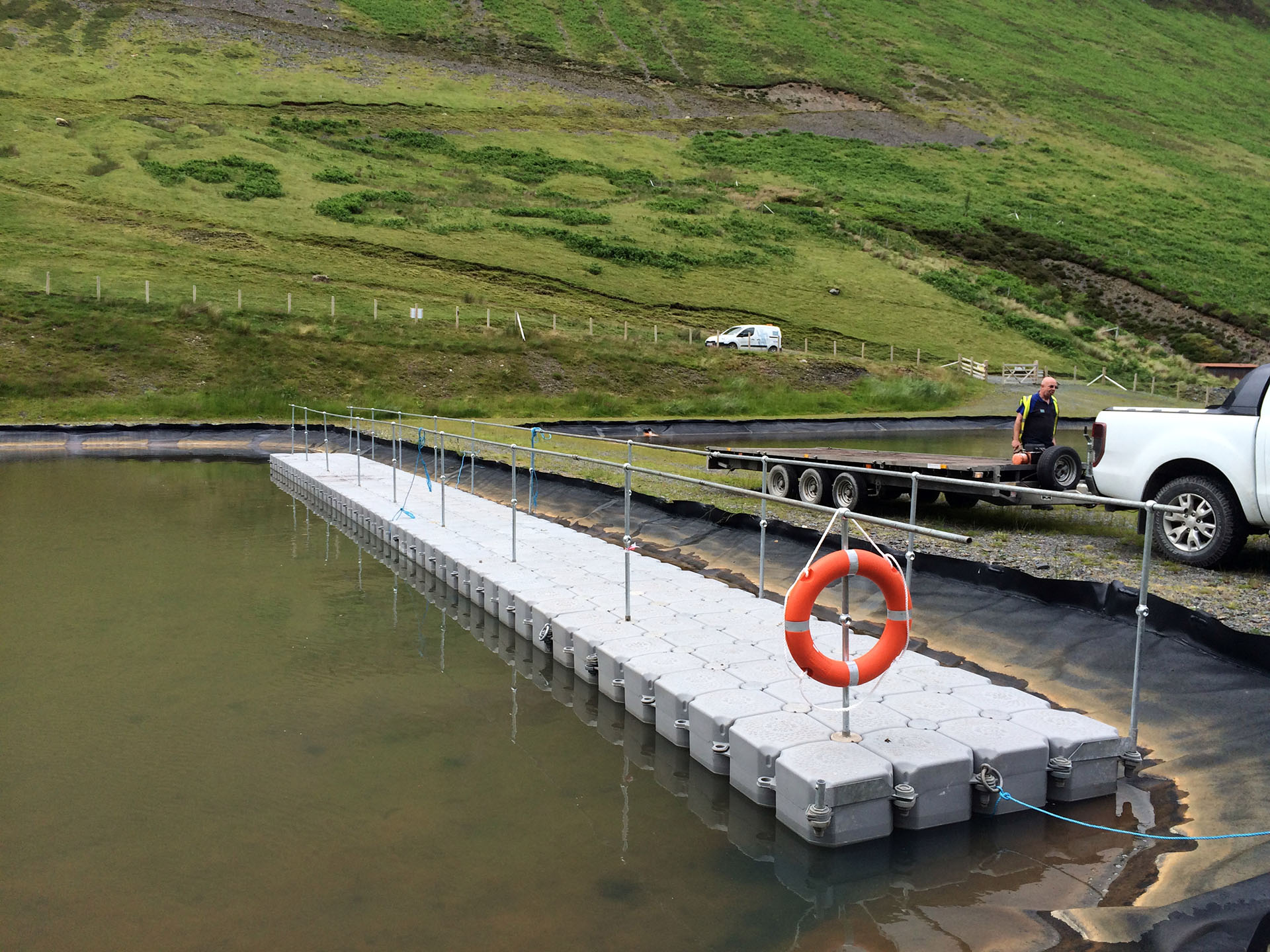 floating walkway with handrails at edge of lake